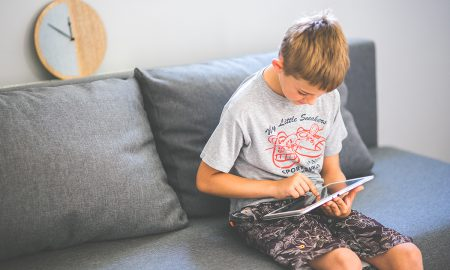 kaboompics-com_young-boy-sitting-on-sofa-with-tablet-pc