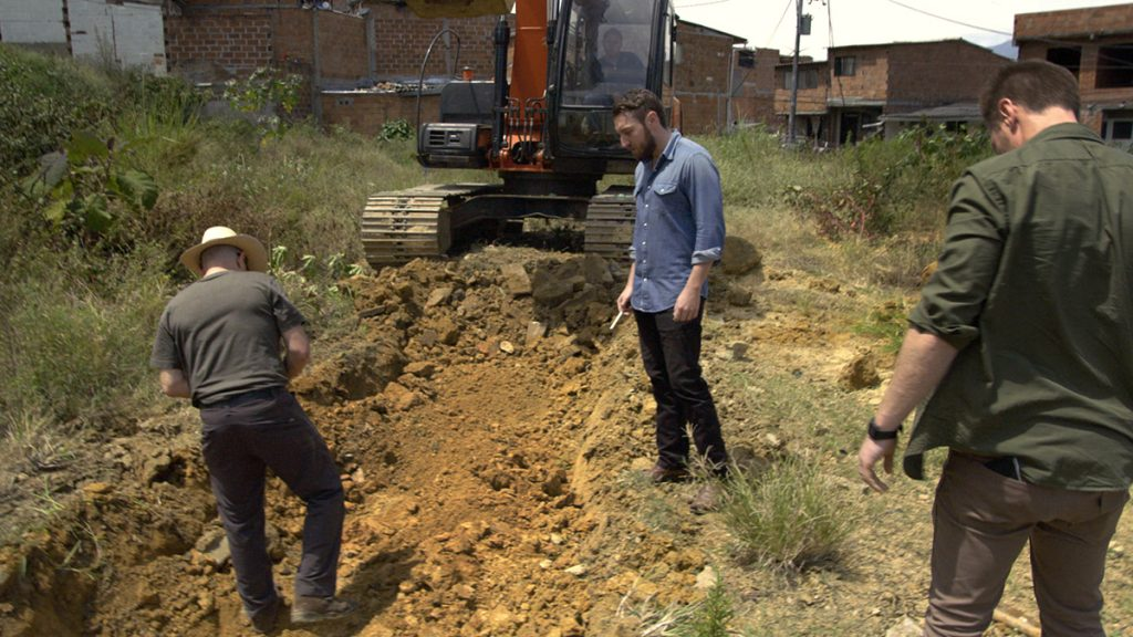 Doug Laux and Paul Bauman examine the unearthed dirt of an empty field in Barrio Pablo Escobar, hoping to find buried cash.