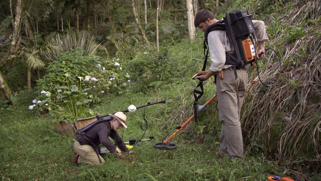 Ground-penetrating-radar team Paul Bauman and Colin Miazga run a metal detector over some jungle ground.